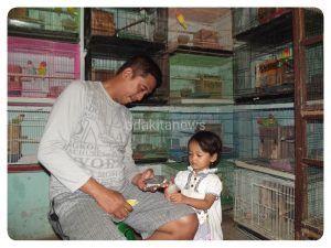 Setio Wahyudi bersama putri bungsunya memberi makan anakan Love Bird.